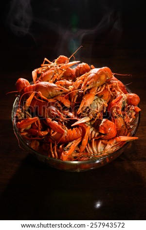 Isolated on black wood table just boiled crayfish with vapor on it - stock photo
