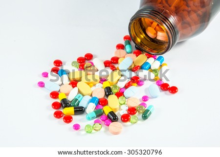 Isolated on white background, Many pills capsules and tablets medicine for patient and doctor. Medicines spilling out of bottle.