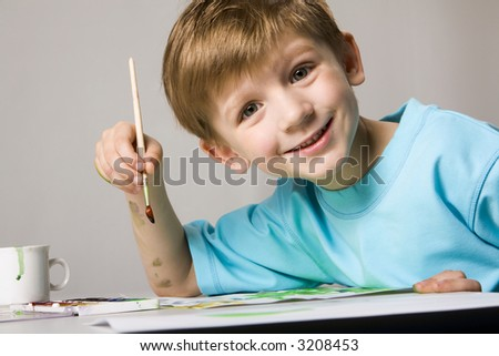 Isolated on white blond boy in blue t-shirt drawing the picture on the table