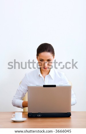Isolated on white portrait of serious brunette businesswoman working on the laptop sitting at the table with a white cup on it - stock photo