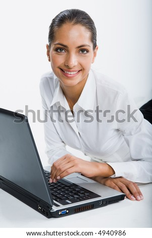 Isolated on white portrait of smiling suntanned woman sitting at the table touching keyboard of opened black laptop gazing at the camera - stock photo