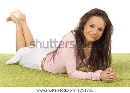 isolated on white young woman lying on the green carpet - stock photo