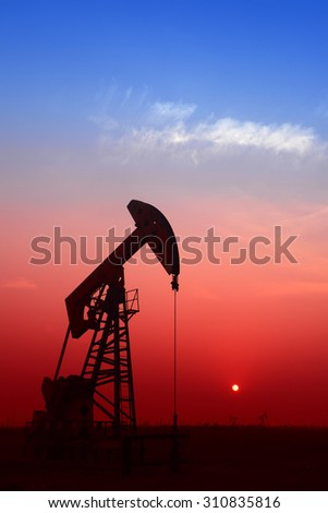 Isolated operation of pumping unit under the setting sun  - stock photo