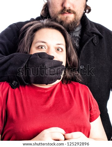 Isolated photo of a woman in red shirt being assaulted from behind by a white male in a black coat, hat and gloves. The mans hand is covering the woman's mouth with fear in her eyes.