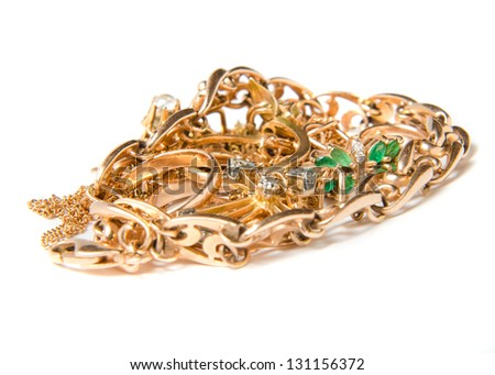 Isolated pile of gold jewelry on white background (chains, necklaces, bracelets, earrings, rings and other scrap gold). - stock photo