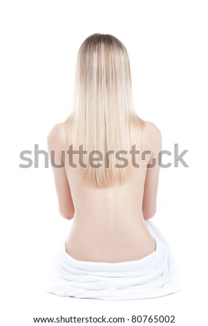 Isolated portrait of a beautiful and sexy young woman, sitting with a bare back. concept of hair, body beauty care. - stock photo