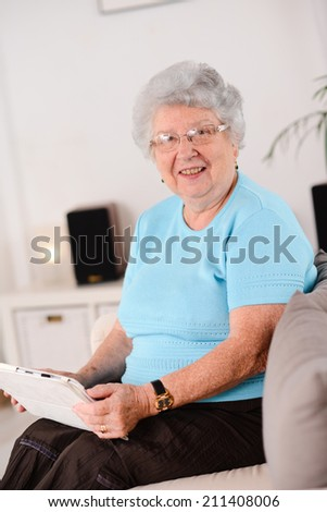 isolated portrait of a cheerful and dynamic elderly woman at home - stock photo