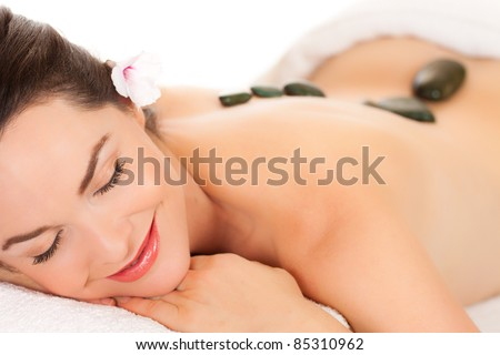 Isolated portrait of an attractive young woman getting a hot stone massage - stock photo