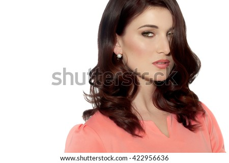 Isolated portrait of beautiful modern woman wearing coral pink top.