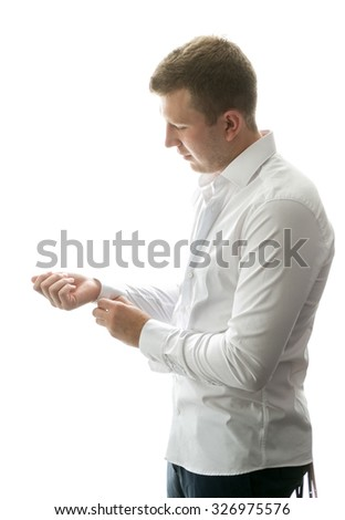 Isolated portrait of stylish man getting ready and buttoning shirt sleeves - stock photo