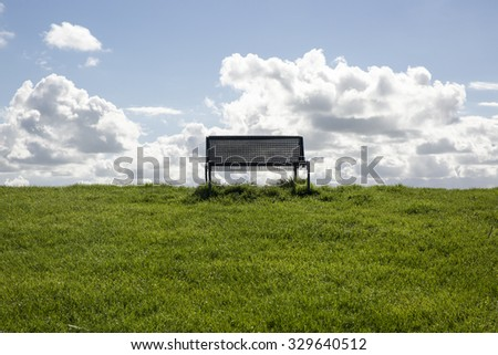 isolated public bench on the top of a dyke with green grass, blue sky and white cloud
