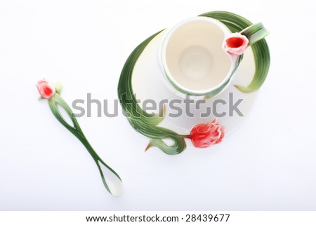 Isolated saucer, cup and spoon decorated with red flower and green color - stock photo
