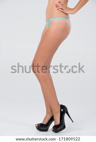 Isolated shoot of long legs, black high heels, and blue panties. - stock photo
