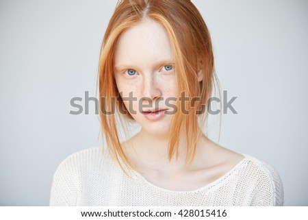 Isolated shot of attractive young redhead female wearing stylish white top looking at the camera with thoughtful and dreamy expression. Pretty teenager with healthy freckled skin posing indoor  - stock photo