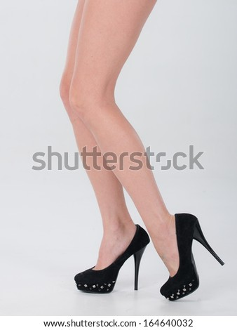 Isolated shot of legs and high heel shoes. - stock photo