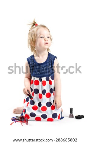 Isolated shot of little fashionista playing with a lipstick, brush for powder and other mommy's stuff
