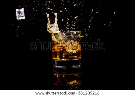Isolated shot of whiskey with splash on black background - stock photo