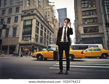 Isolated smiling young businessman on a city street - stock photo
