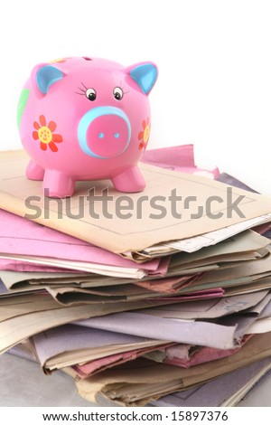 Isolated stack of folder with piggy bank at the top shot over white background - stock photo
