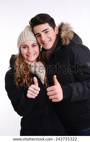 isolated studio portrait of a happy young couple in winter outfit - stock photo