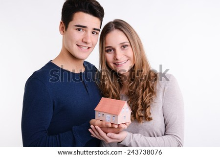 isolated studio portrait of successful young couple showing house reduced model - stock photo