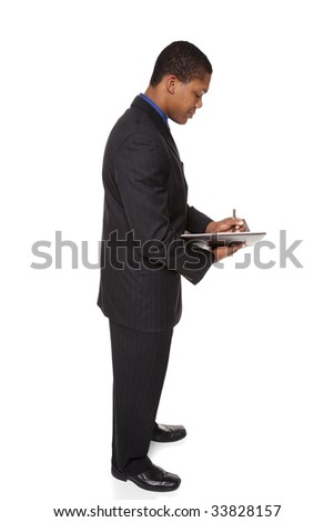Isolated studio shot of a businessman standing and writing in a notebook he is holding. - stock photo