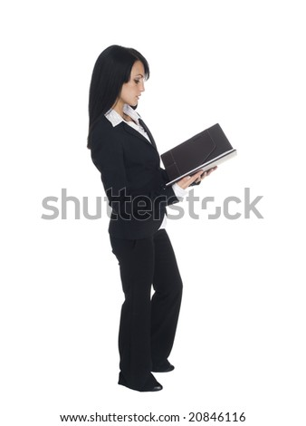 Isolated studio shot of a businesswoman standing and reading from a note book. - stock photo