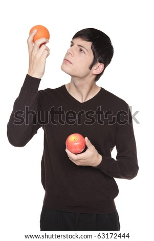 Isolated studio shot of a Caucasian man looking at fruit comparing an apple to an orange.
