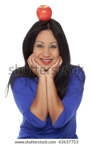 Isolated studio shot of a Latina woman with braces and an apple on her head. - stock photo