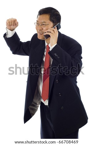 Isolated studio shot of a successful surprised Asian American businessman with clenched fist using mobile phone. Celebrating some happy news