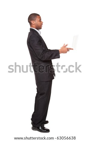 Isolated studio shot of an African American businessman standing and looking warily at a laptop computer he is holding out in his hands. - stock photo