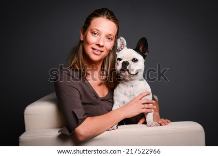 isolated studio shot of beautiful young woman with her pet little dog french bulldog