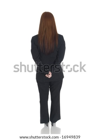 Isolated studio shot of the back side of a businesswoman standing with her hands clasped behind her back.