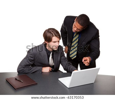 Isolated studio shot of two businessmen working on a laptop at a conference table. - stock photo