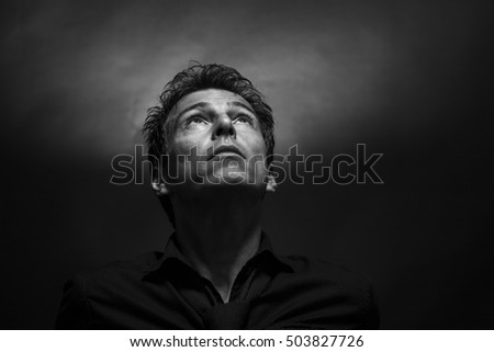 Isolated thinking man face looking up. Low key , black and white portrait. Hope concept