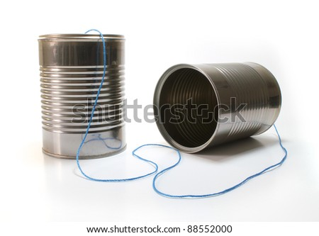 Isolated tin can telephone with blue thread. - stock photo
