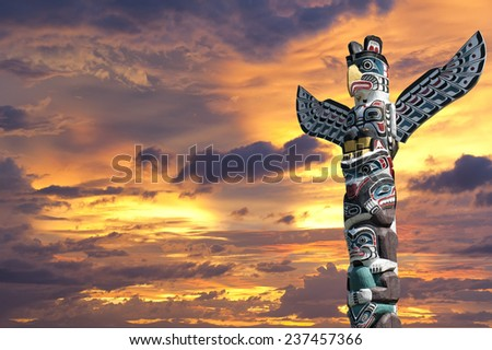 Isolated totem wood pole in the gold sunset background - stock photo