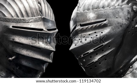 isolated two knights on the black background with steel helmets - stock photo