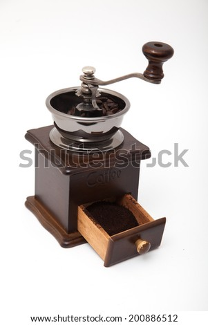 Isolated vintage coffee bean grinder and fresh ground coffee next to coffee bean