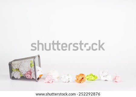 isolated wastebasket full of color waste paper - stock photo