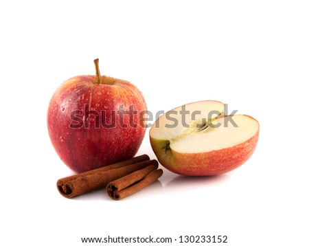 Isolated wet red apple with sliced half and cinnamon pods on a white background. Fresh diet fruit. Healthy fruit with vitamins.