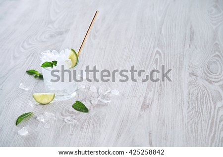 Isolated whiskey rox glass full of crashed ice cubes and lime with golden drinking straw on wooden rustic table Preparation of mojito or other cocktail process - stock photo