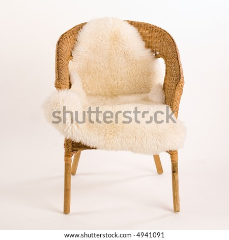 Isolated wicker chair with sheep fell - stock photo