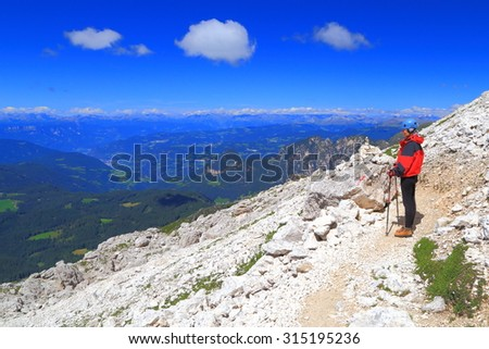 Isolated woman admires the view in the valley in sunny day of summer, Catinaccio massif, Dolomite Alps, Italy - stock photo