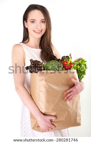 Isolated woman holding a shopping bag full of vegetables on white background - stock photo