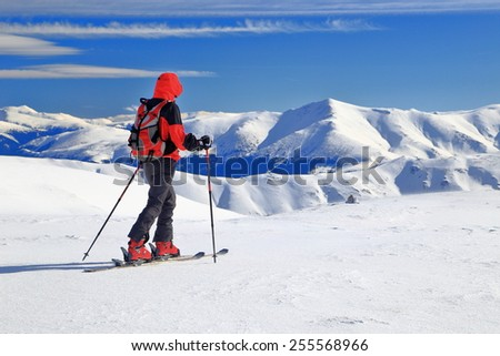 Isolated woman moving on touring skies along snow covered plateau high on alpine area - stock photo