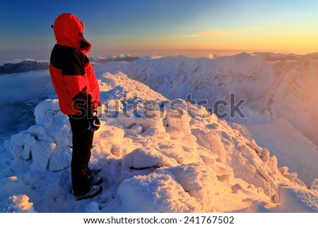Isolated woman standing on snow covered mountain at sunset - stock photo