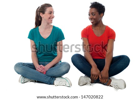 Isolated women sitting on the studio floor - stock photo