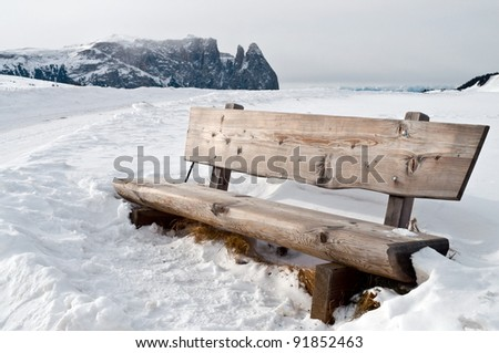 Isolated wooden bench on snow scape in dolomiti, Alps - stock photo