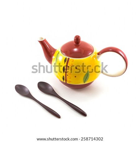 Isolated Yellow Ceramic Tea Pot with Two Wooden Spoons on White Background
